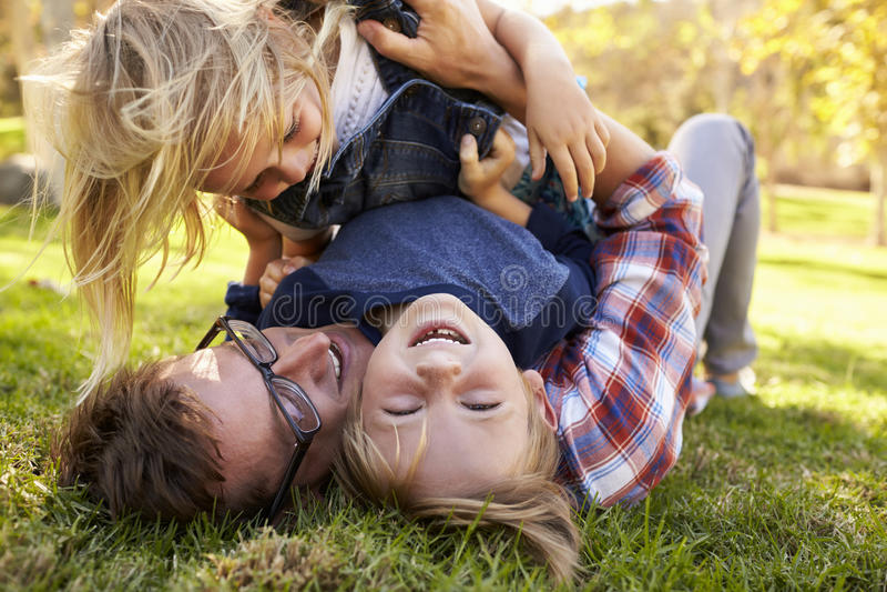 Två unga ungar som överst ligger av deras farsa i en parkera fotografering för bildbyråer
