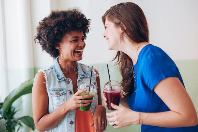 Två unga vänner som har ny fruktsaft och samtal royaltyfri foto