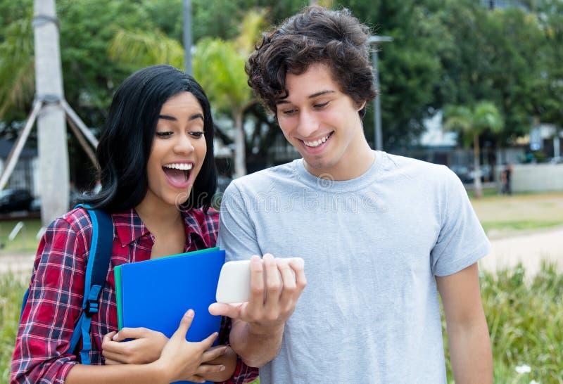 Två unga vuxna människor som håller ögonen på videogemet på mobiltelefonen royaltyfria bilder