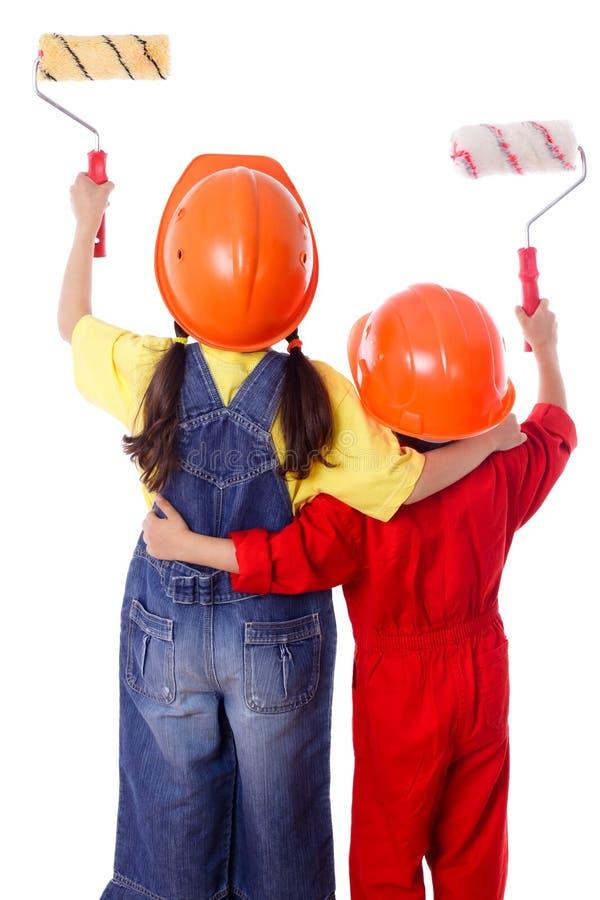 Två ungar i overall med målarfärgrullar fotografering för bildbyråer