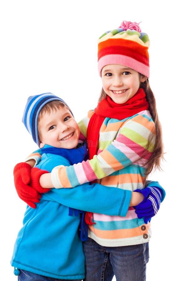 Två ungar i vinterkläder som kramar varje andra royaltyfri fotografi
