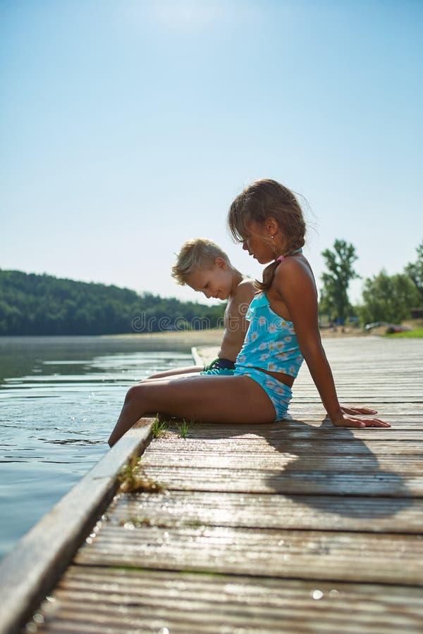 Två ungar kyler ner deras fot i sjön i sommar royaltyfri fotografi