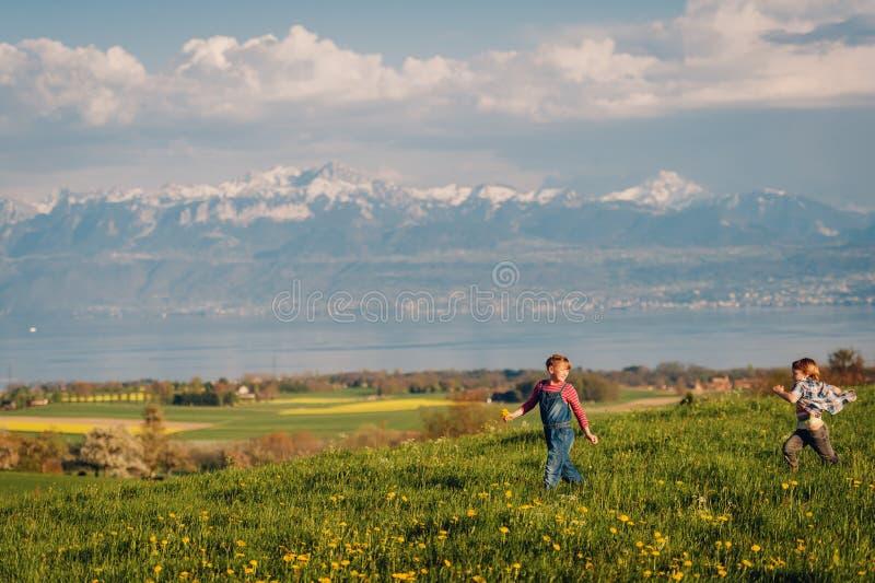 Två ungar, liten broder och storasyster som tillsammans utomhus spelar i schweiziska fält med sikt på sjöGenève royaltyfria foton