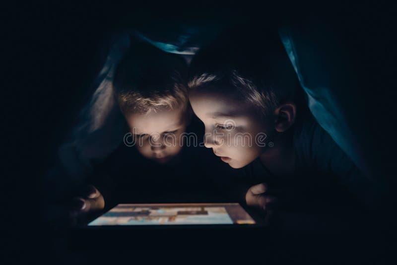 Två ungar med minnestavladatoren i ett mörkt rum arkivbilder
