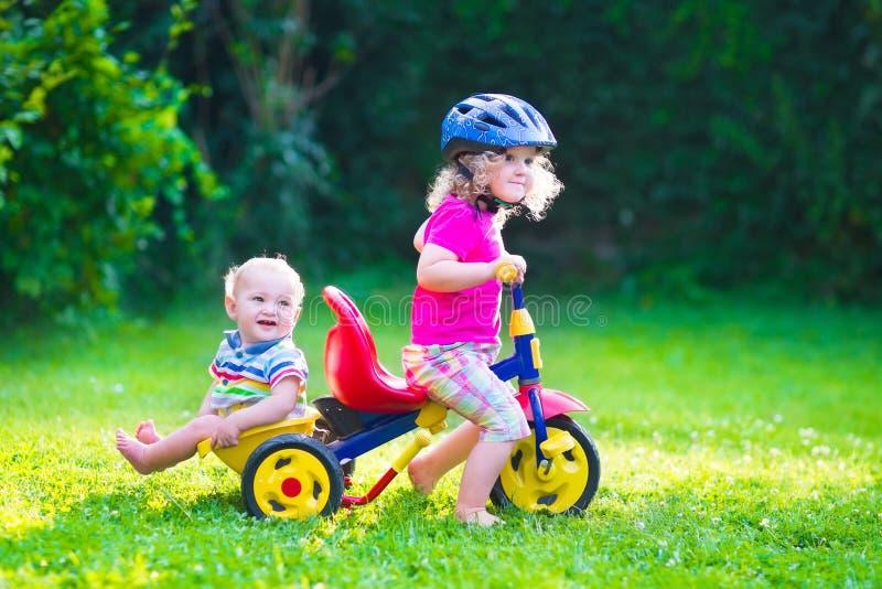 Två ungar på en cykel royaltyfri bild
