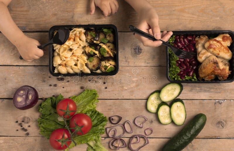 Två ungar rymmer skeden och gaffeln under matbehållaren med grillade fega vingar, blå handduk royaltyfria bilder