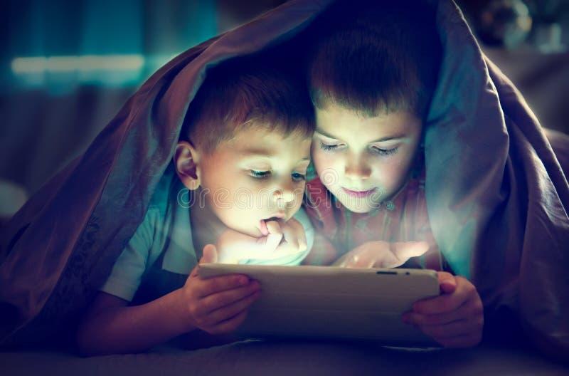 Två ungar som använder minnestavlaPC på natten royaltyfri fotografi