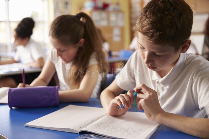 Två ungar som arbetar på deras skrivbord i grundskola för barn mellan 5 och 11 år, slut upp royaltyfri foto