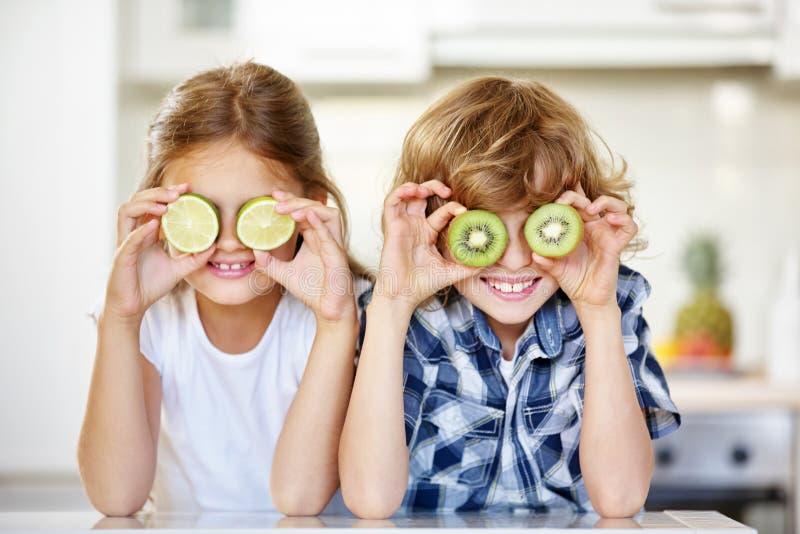 Två ungar som döljer ögon bak frukter royaltyfria bilder