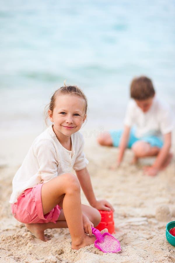 Två ungar som leker på stranden royaltyfri fotografi
