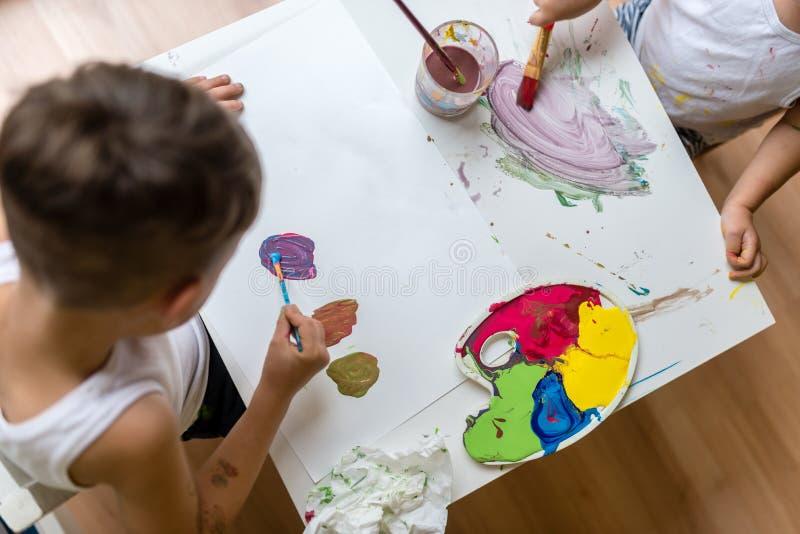 Två ungar som målar med vattenfärger med borsten royaltyfri bild
