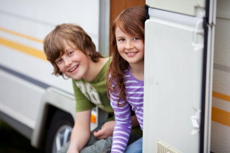 Två ungar som sitter i dörröppning av RV royaltyfri foto