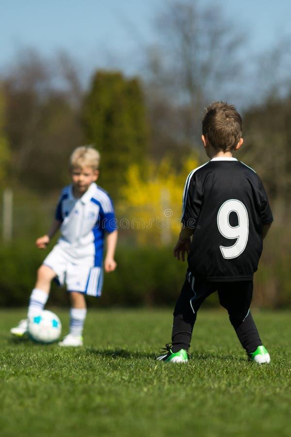 Två ungar som spelar fotboll arkivfoton