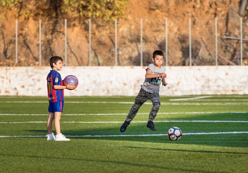 Två ungar som spelar fotboll i ett fotbollfält ett av dem med hydraen för Barcelona skjortaiin, Grekland arkivbild