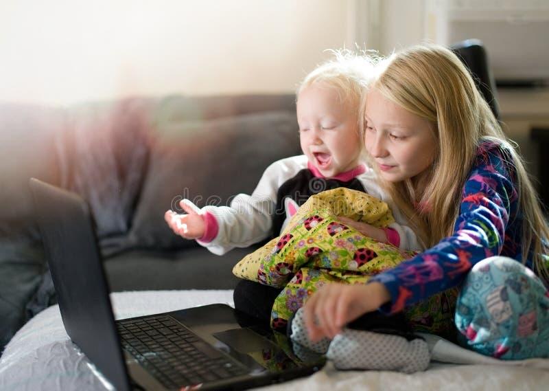 Två ungar som spelar med bärbar datordatoren arkivfoto