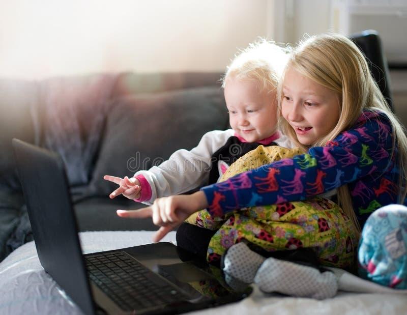 Två ungar som spelar med bärbar datordatoren fotografering för bildbyråer