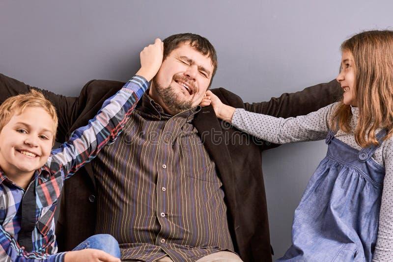 Två ungar som spelar med deras fader arkivbild