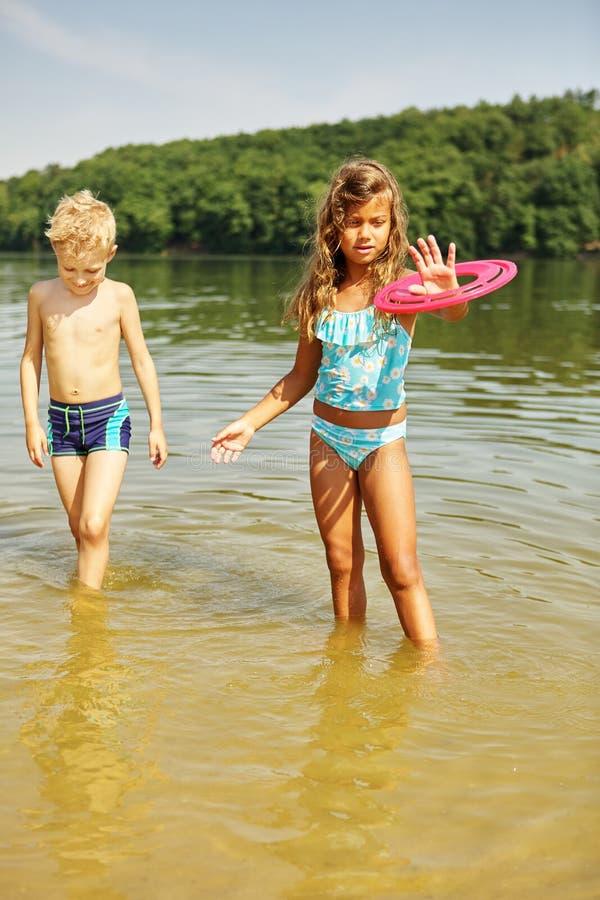Två ungar som spelar med en frisbee i sjön arkivfoto