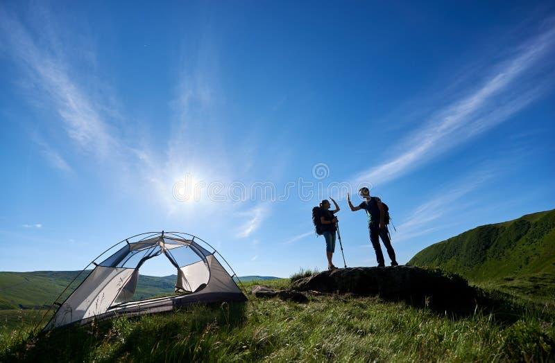 Två ungdomari ryggsäckar och trekking pinnar ger sig höjdpunkt fem nära att campa i berg royaltyfria bilder