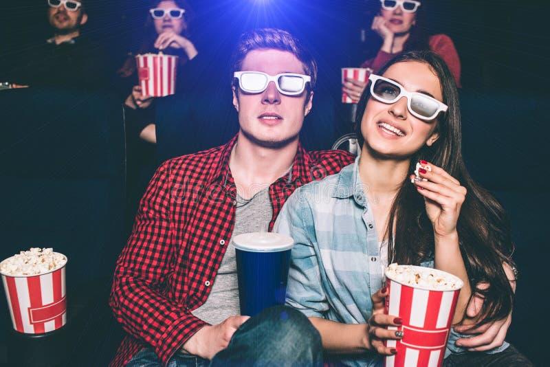 Två ungdomarsitter nästan De har speciala exponeringsglas på deras framsidor som håller ögonen på film Flickan är arkivfoton