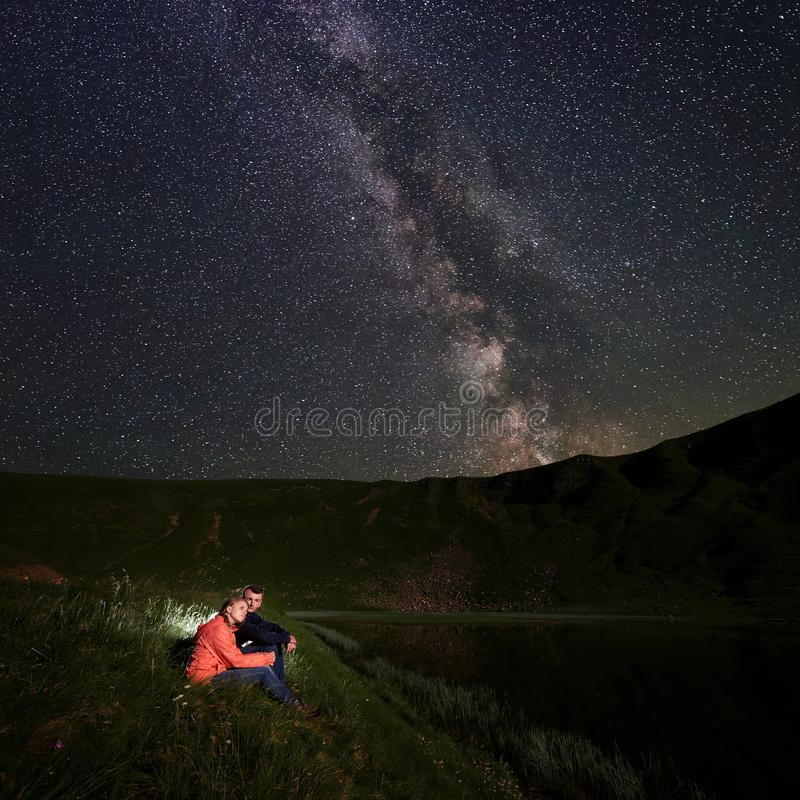 Två ungdomarsitter på sjön på bakgrund av väldiga berg under den stjärnklara himlen arkivbilder