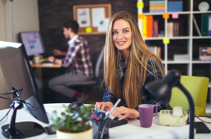 Två ungdomarsom arbetar på deras datorer, fokus på kvinnan arkivbilder