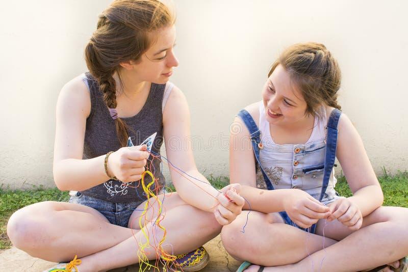 Två ungdomarsom gör armband royaltyfria bilder