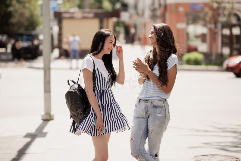 Två ungdomliga nätta slanka flickor, bärande tillfällig dräkt, ställning på gatan och pratstund royaltyfria foton