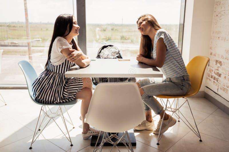 Två ungdomliga nätta slanka flickor med mörkt hår, bärande tillfällig dräkt, sitter på tabellen bredvid de och pratstund i a arkivfoton