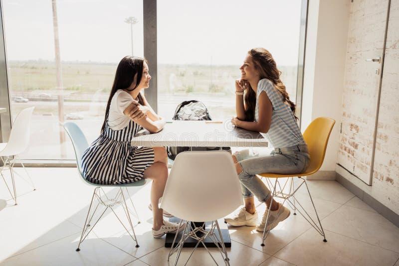Två ungdomliga nätta slanka flickor med mörkt hår, bärande tillfällig dräkt, sitter på tabellen bredvid de och pratstund i a royaltyfri foto