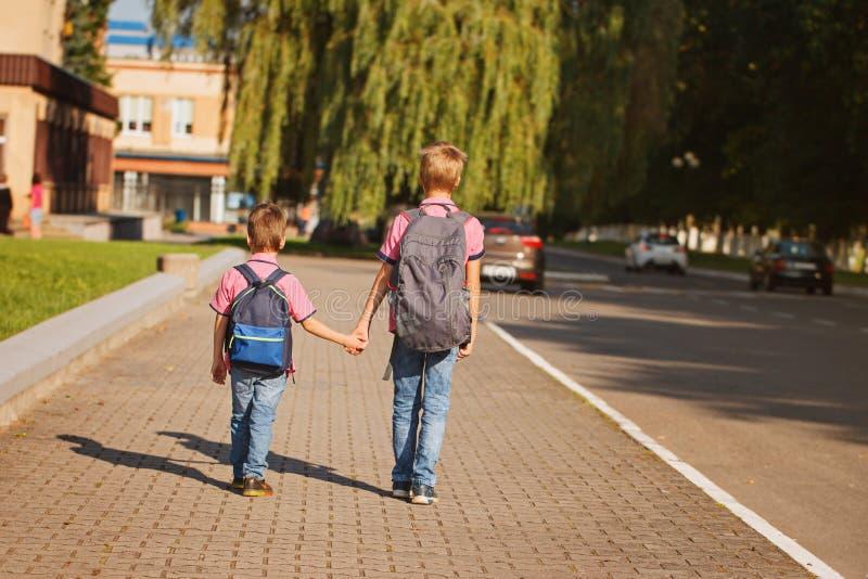 Två ungebröder med ryggsäcken som är hållande på händer som går till skolan tillbaka sikt royaltyfria bilder