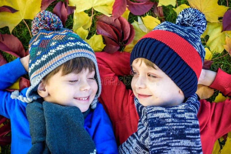 Två ungepojkar för liten broder som ligger i höstsidor i färgrika tillfälliga kläder Det lyckliga syskonet som har gyckel i höst, fotografering för bildbyråer