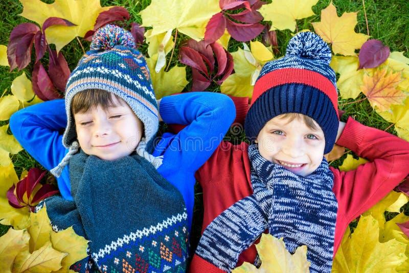 Två ungepojkar för liten broder som ligger i höstsidor i färgrika tillfälliga kläder Det lyckliga syskonet som har gyckel i höst, royaltyfri foto