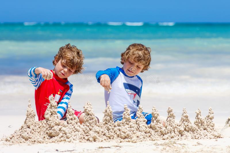 Två ungepojkar som bygger sandslotten på den tropiska stranden royaltyfri foto