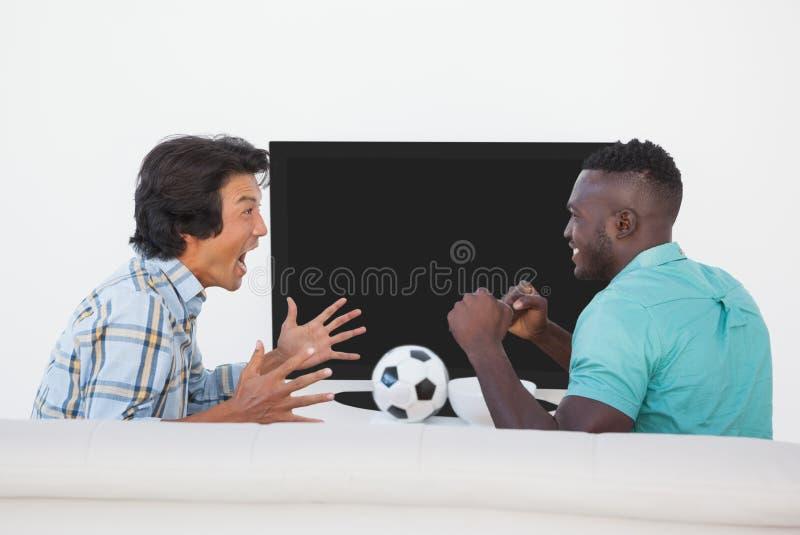 Två upphetsade fotbollfans som håller ögonen på tv arkivfoto