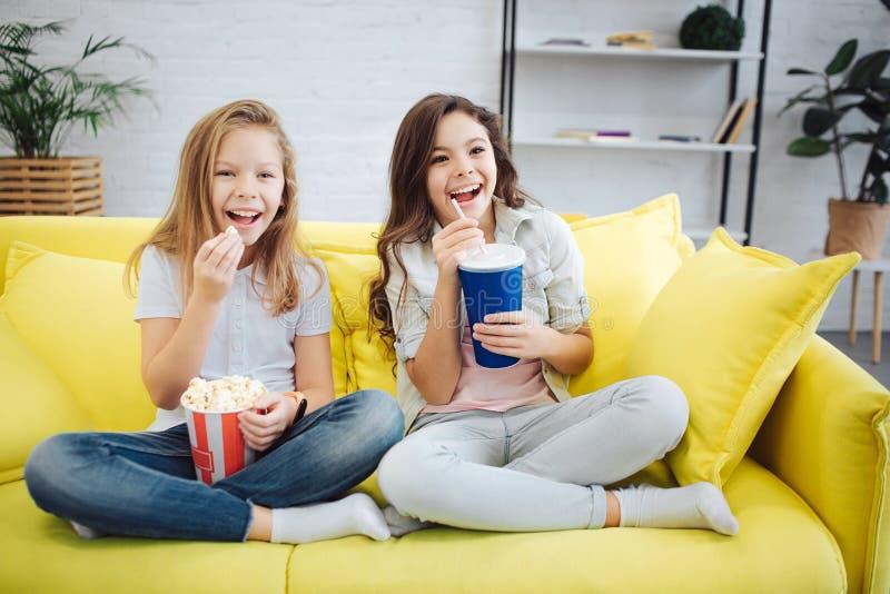 Två upphetsade tonåringar sitter på soffan och klockan framåtriktat De rymmer busket med popcorn och koppen av cola Flickan hålle arkivbild