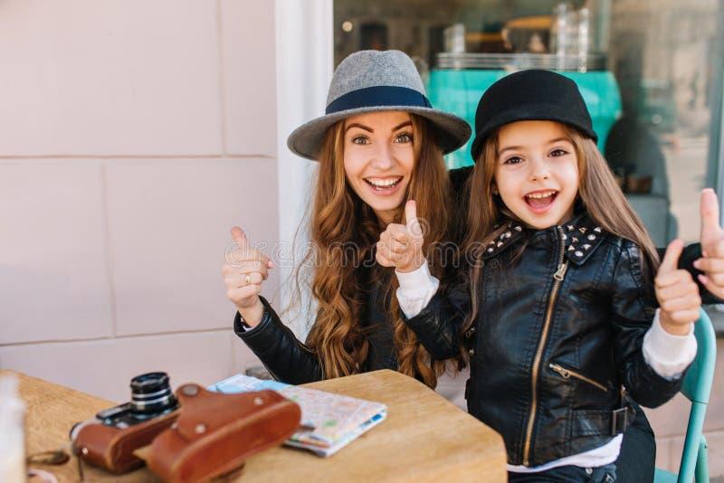 Två upphetsade turister som poserar på den utomhus- restaurangen med tummar upp väntande på lunch efter, går St?ende av stilfullt fotografering för bildbyråer