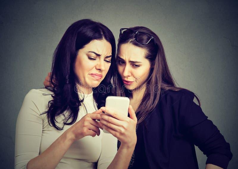 Två upprivna vänkvinnor som beskådar på linjen innehåll på en smart telefon royaltyfri fotografi