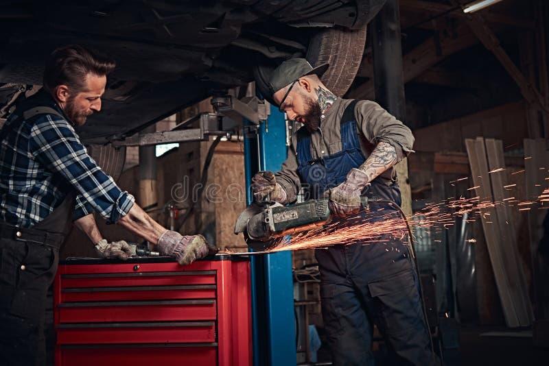 Två uppsökte den auto mekanikern i en likformig och säkerhetsexponeringsglasarbete med en vinkelmolar, medan stå under lyftande b arkivbild