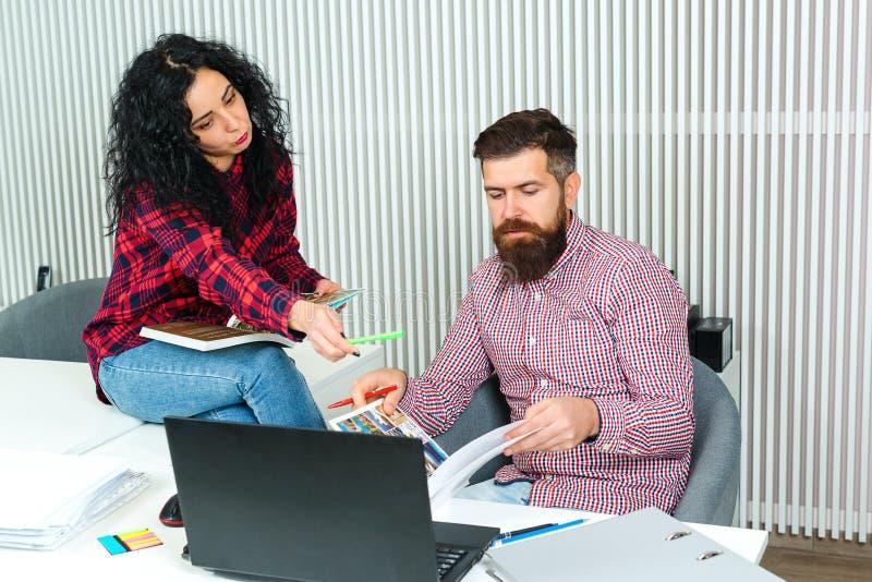 Två upptagna kollegor som tillsammans arbetar Teamwork Nytt projekt på modern arbetsplats Två hipstersformgivare som diskuterar a royaltyfria bilder