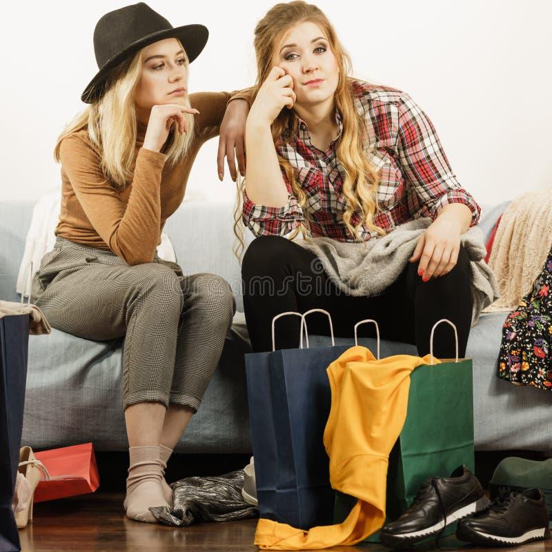 Två uttråkade kvinnor bredvid shoppingpåsar arkivfoto