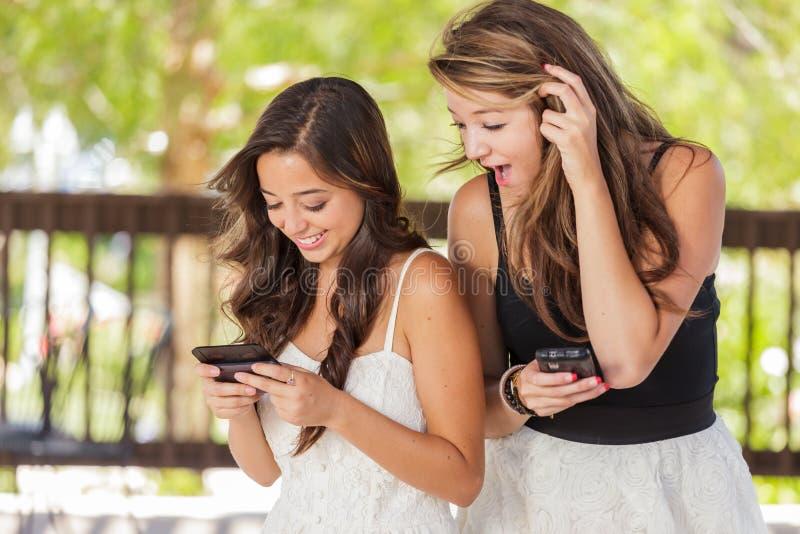 Två uttrycksfulla tonåriga flickvänner för blandat lopp som använder deras smarta cell Pho arkivbilder