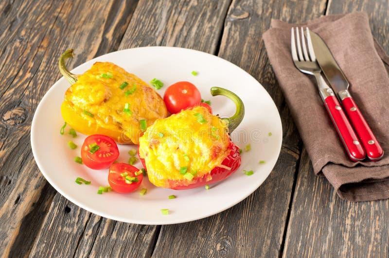 Två välfyllda peppar med kött, champinjoner och tomater och ost arkivbild