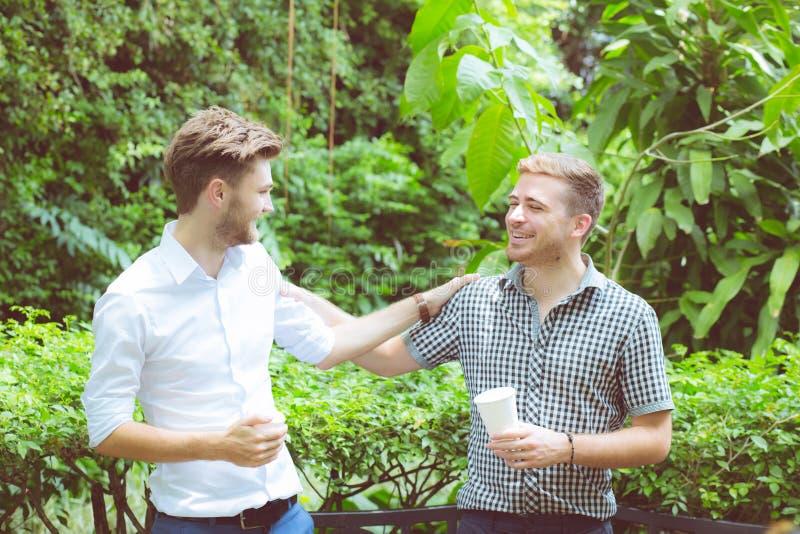 Två vänmän som talar att stå i en trädgård arkivfoton