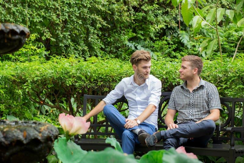 Två vänmän som talar sammanträde i en trädgård royaltyfria foton