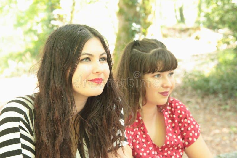 Två vänner eller systrar i en skog fotografering för bildbyråer