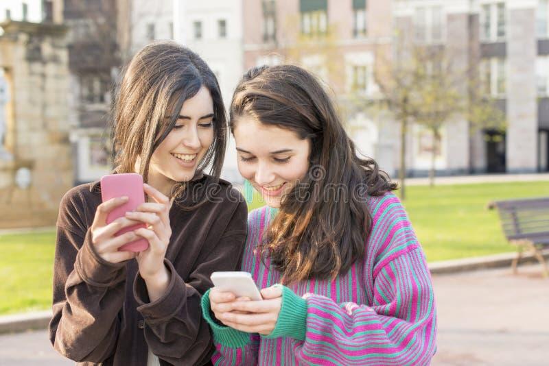 Två vänner för hipsterglädjekvinna som använder den smarta telefonen arkivbild