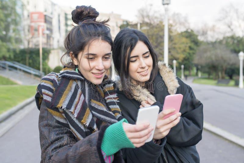 Två vänner för hipsterglädjekvinna som använder den smarta telefonen arkivfoto