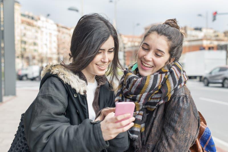 Två vänner för hipsterglädjekvinna som använder den smarta telefonen arkivfoton