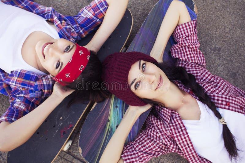 Två vänner för tonårs- flickor för brunett i hipster utrustar (jeans kortsluter, keds, plädskjorta, hatt), med en skateboard på p arkivbild